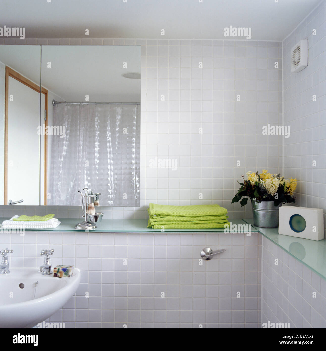 Green towels on vanity unit in modern white bathroom - Stock Image