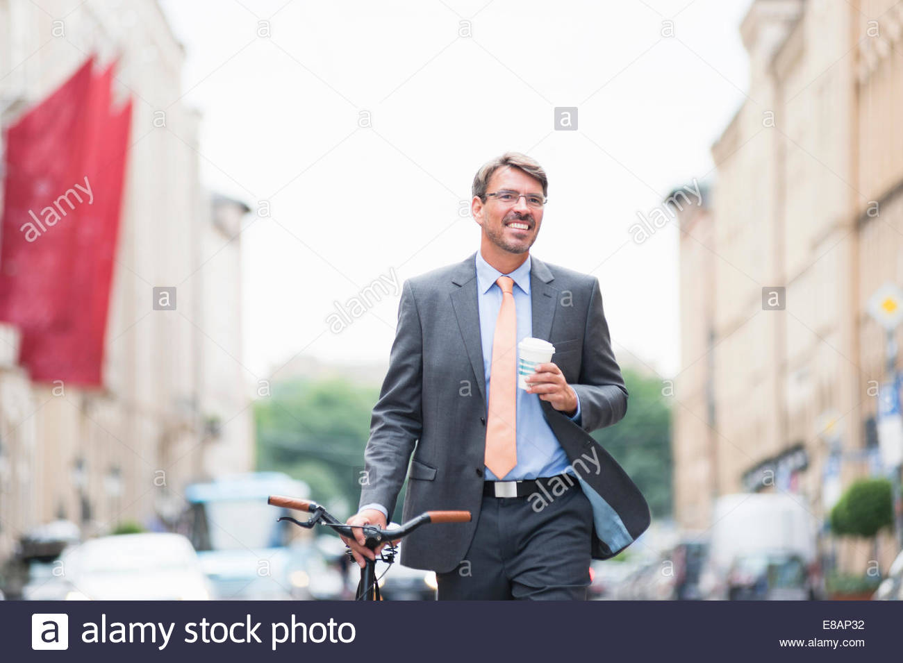 Mature businessman pushing bicycle in street and drinking takeaway coffee - Stock Image