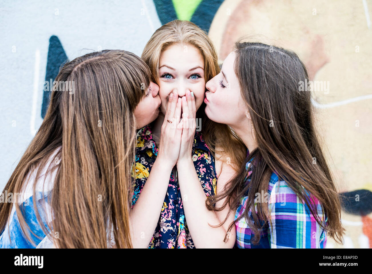 Woman delighted by friends kissing her on cheek - Stock Image