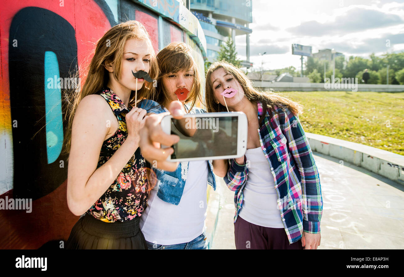 Friends taking selfie wearing fake lips and moustache, mural in background - Stock Image