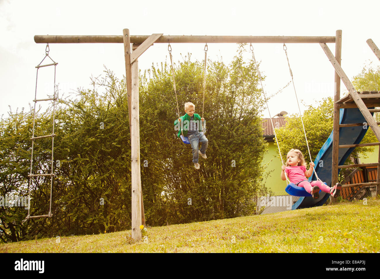 Brother and sister playing on swings in garden Stock Photo: 73995590 ...