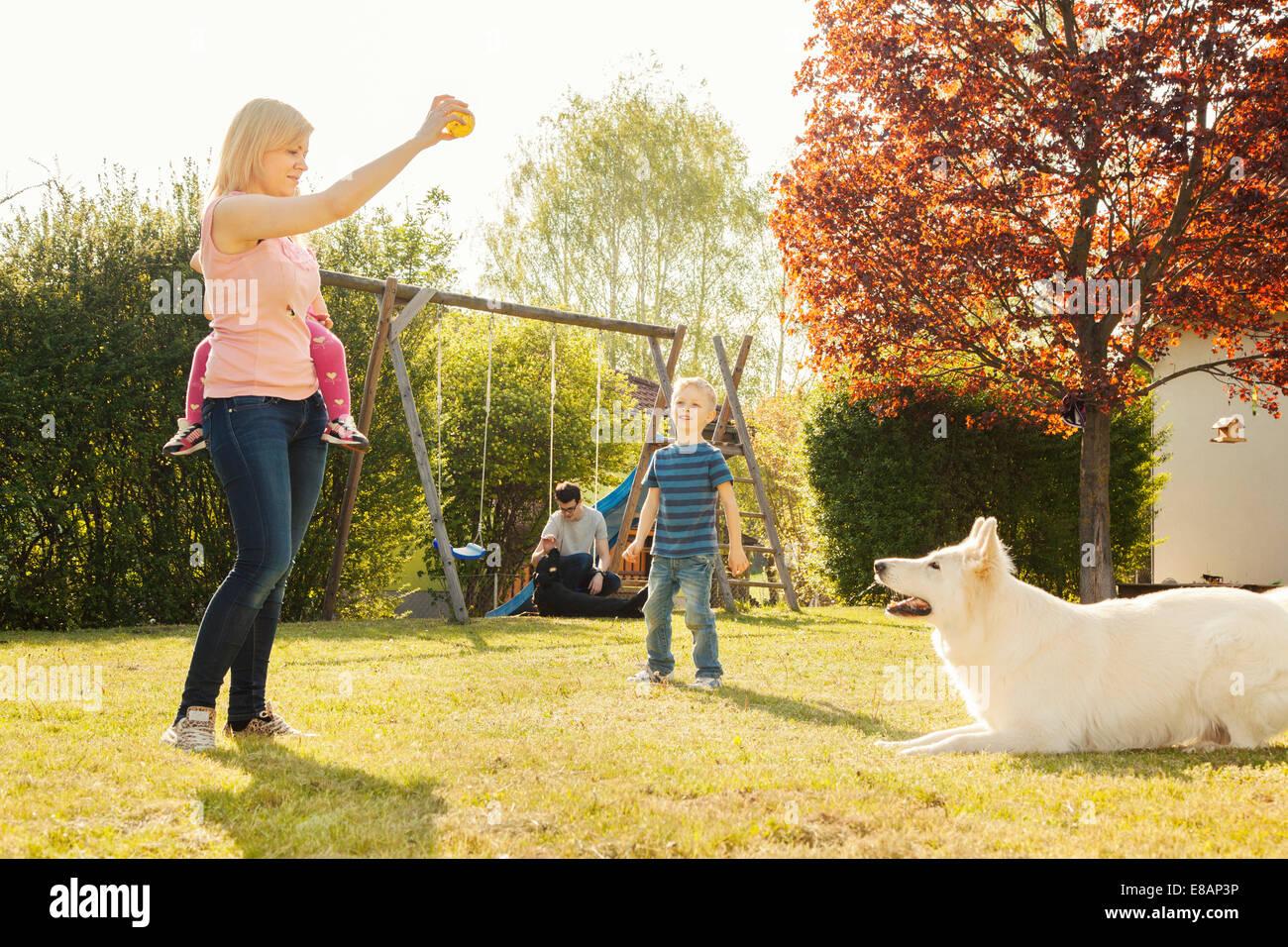 Family in garden training dog - Stock Image
