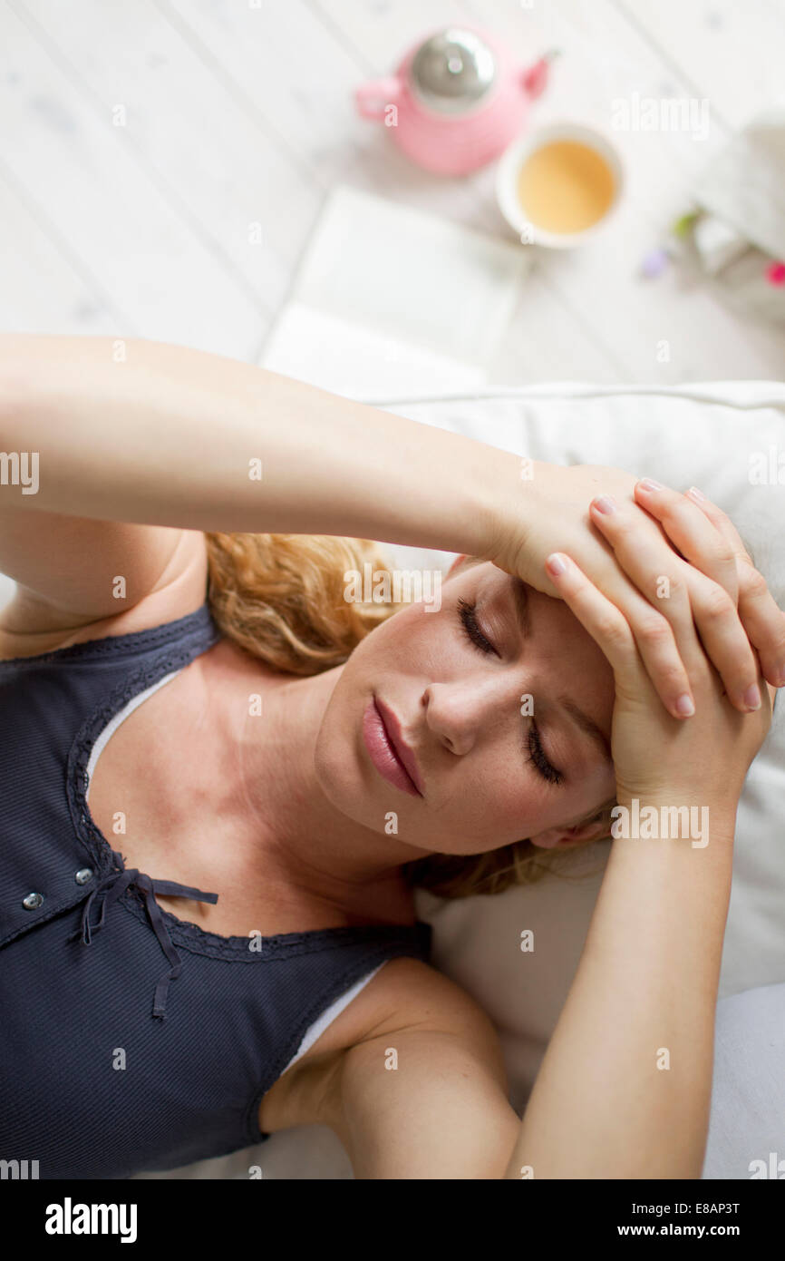 Woman lying on sofa with hands on head - Stock Image