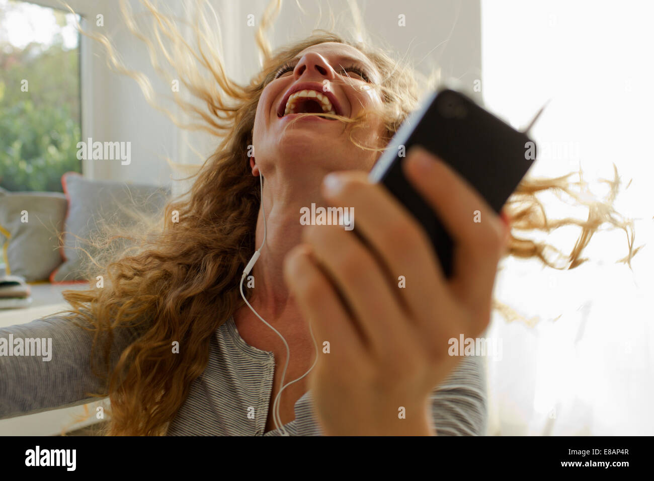 Woman dancing to music on smartphone - Stock Image