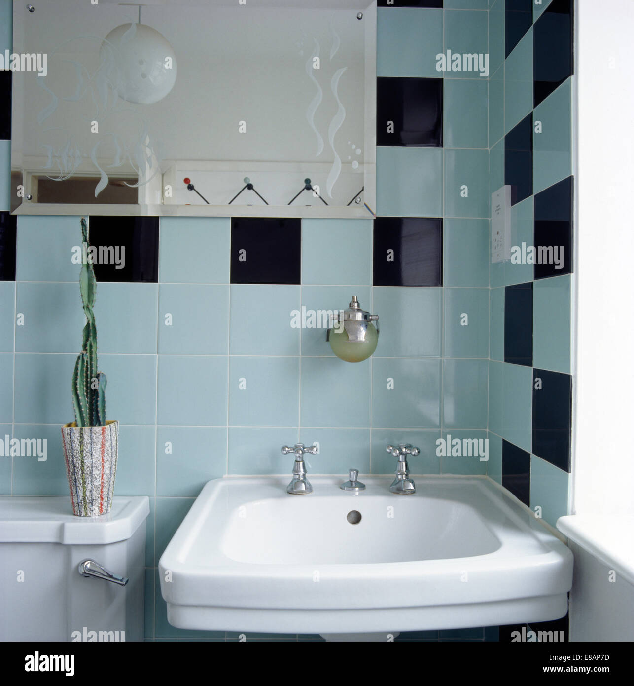 Pale turquoise and black tiles on wall above basin in fifties style ...
