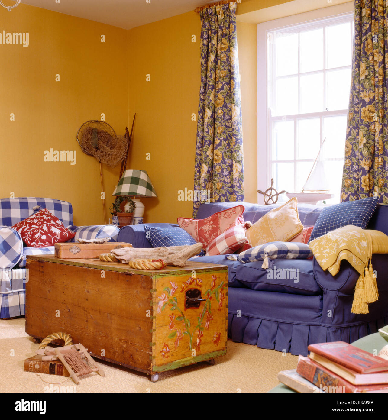 Painted chest and blue sofa in yellow coastal living room with Stock ...