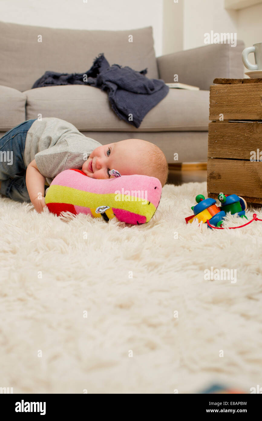 Baby girl lying on rug with soft toy in sitting room - Stock Image