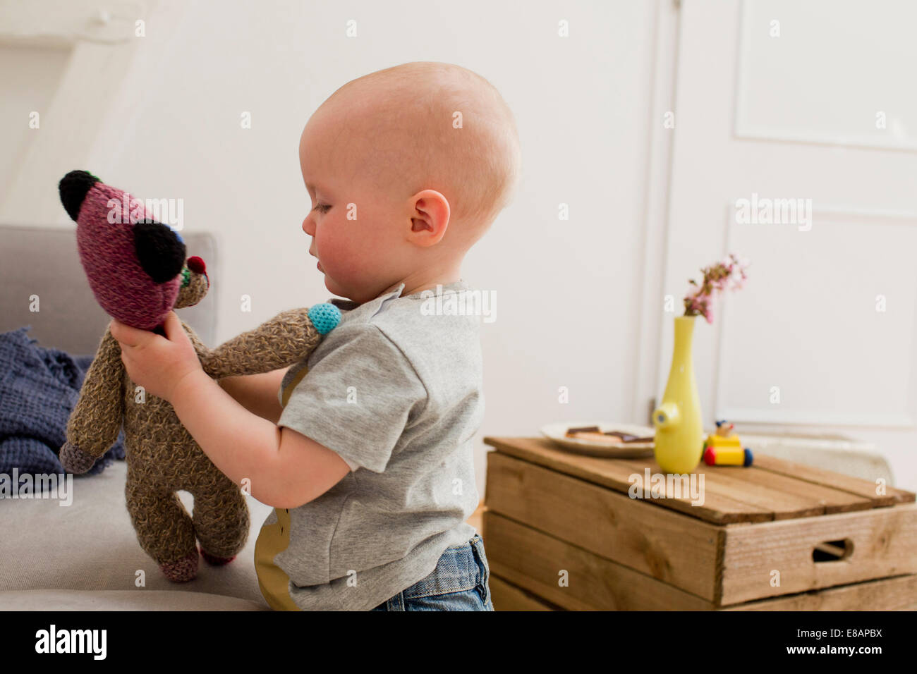 Baby girl pointing playing with teddy bear in sitting room - Stock Image