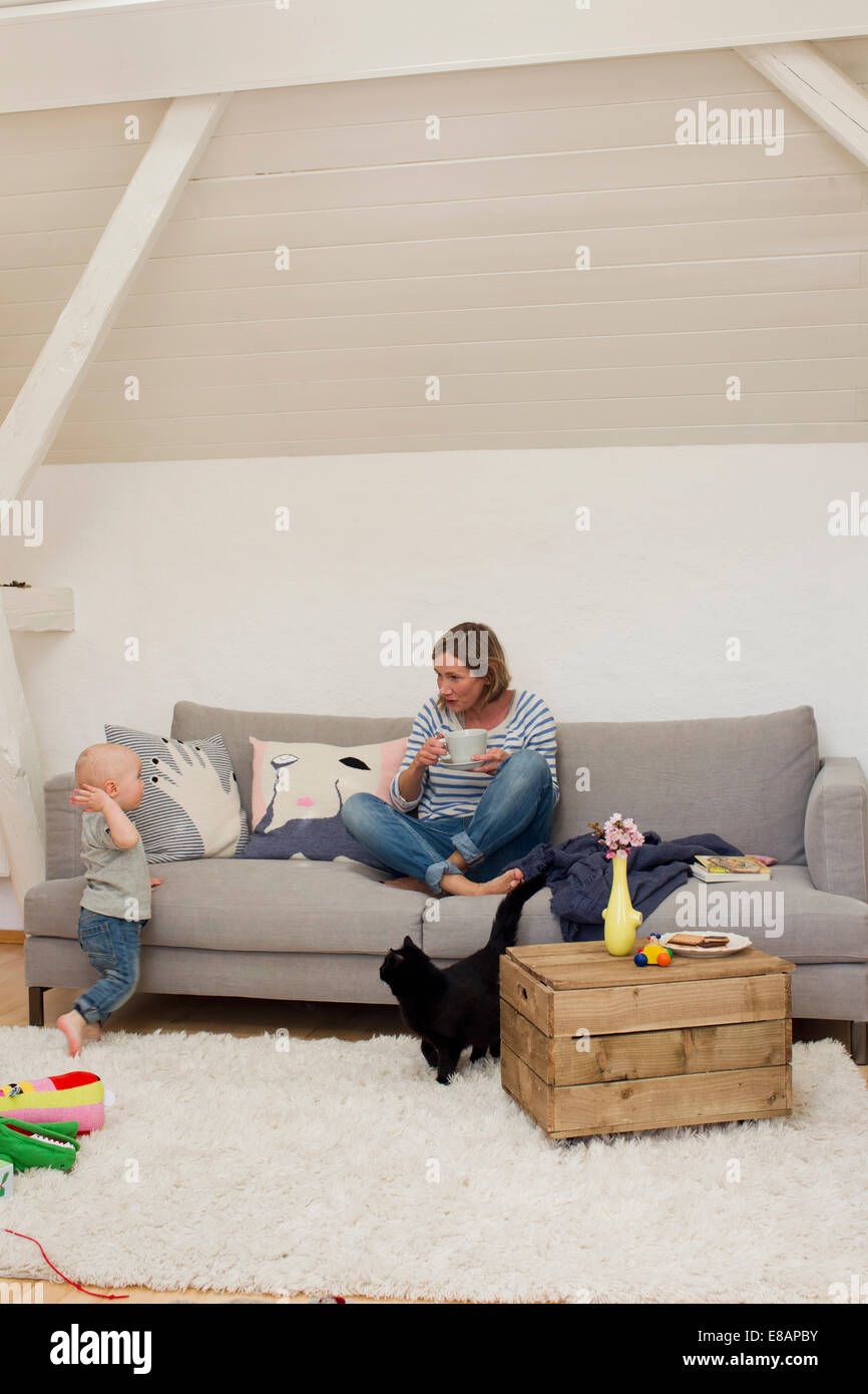 Mature mother drinking coffee with attention seeking baby daughter - Stock Image