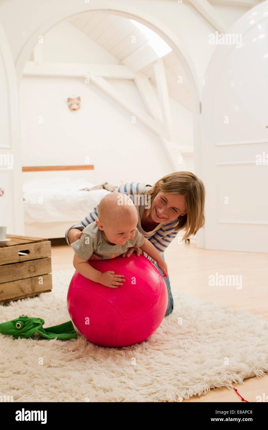 Mature mother and baby daughter on top of exercise ball in sitting room - Stock Image