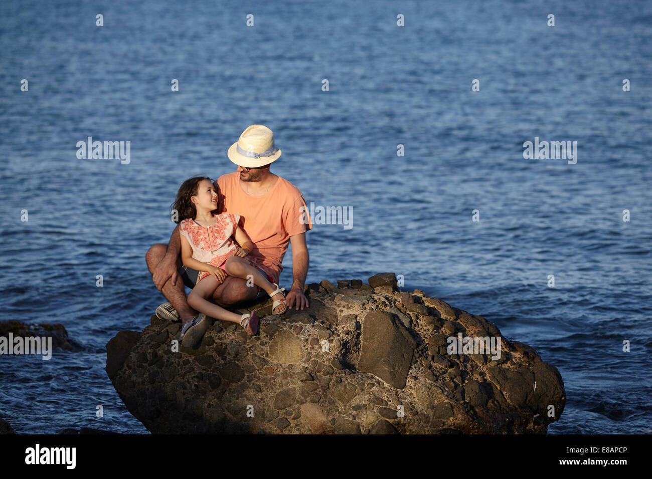 Father and daughter, sitting on rock in sea, Costa Brava, Catalonia, Spain - Stock Image