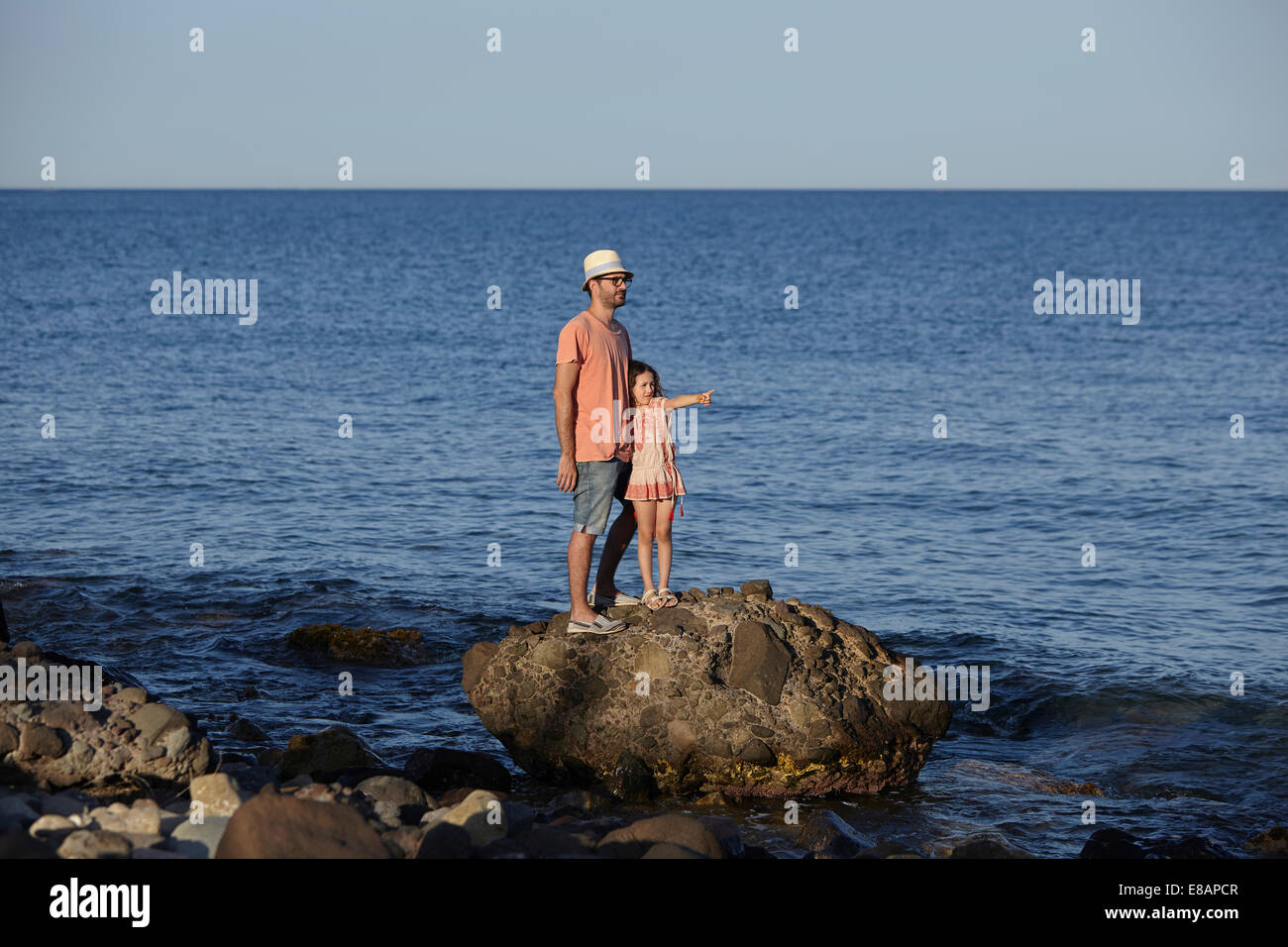 Father and daughter standing on rock in sea, Costa Brava, Catalonia, Spain - Stock Image