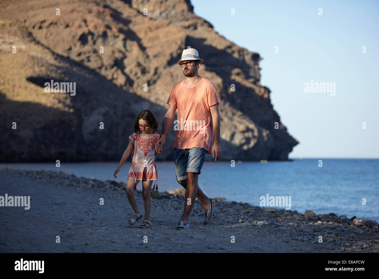 Father and daughter walking by the sea, Costa Brava, Catalonia, Spain - Stock Image
