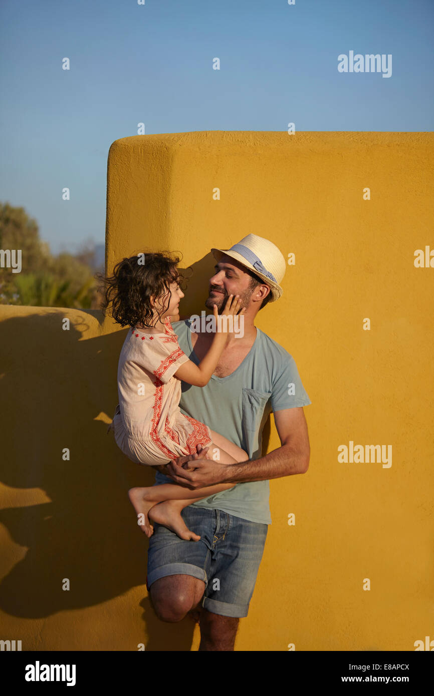 Father holding daughter, leaning against wall, Costa Brava, Catalonia, Spain - Stock Image