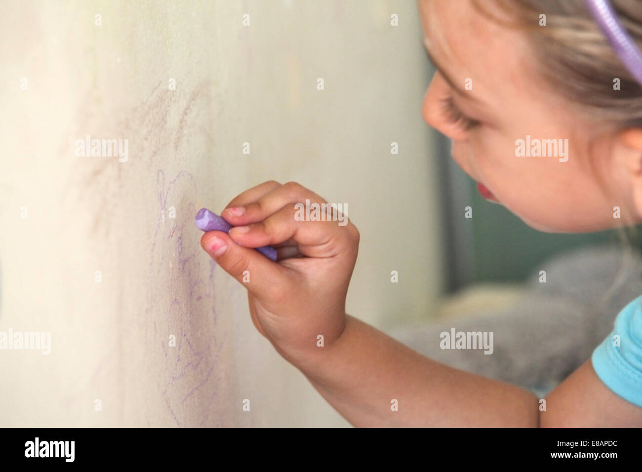 Young girl drawing on wall with chalk - Stock Image