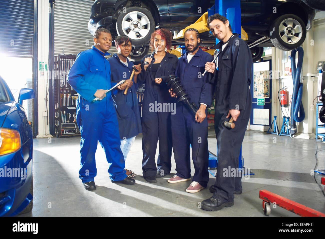 Portrait of five college students beneath car in garage workshop - Stock Image