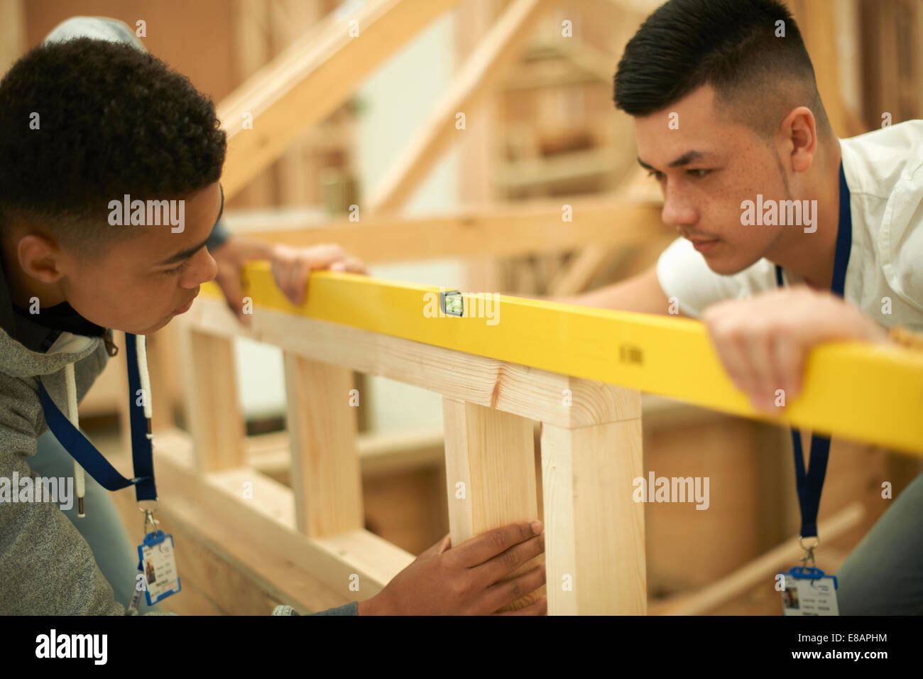 Two male college students using spirit level on frame in woodworking workshop - Stock Image