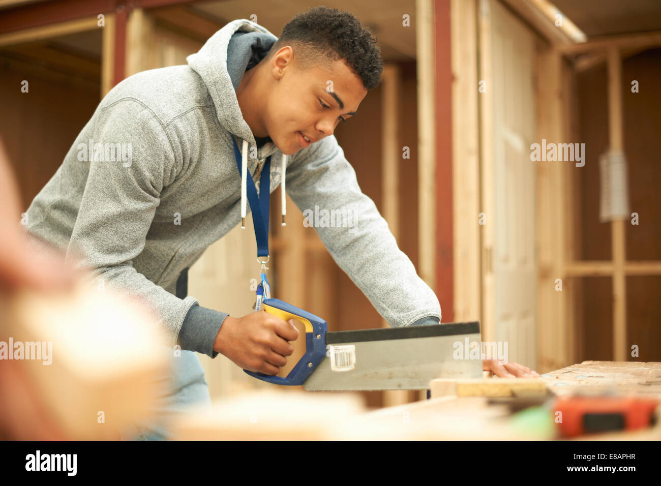 Male college student using saw in woodworking workshop - Stock Image