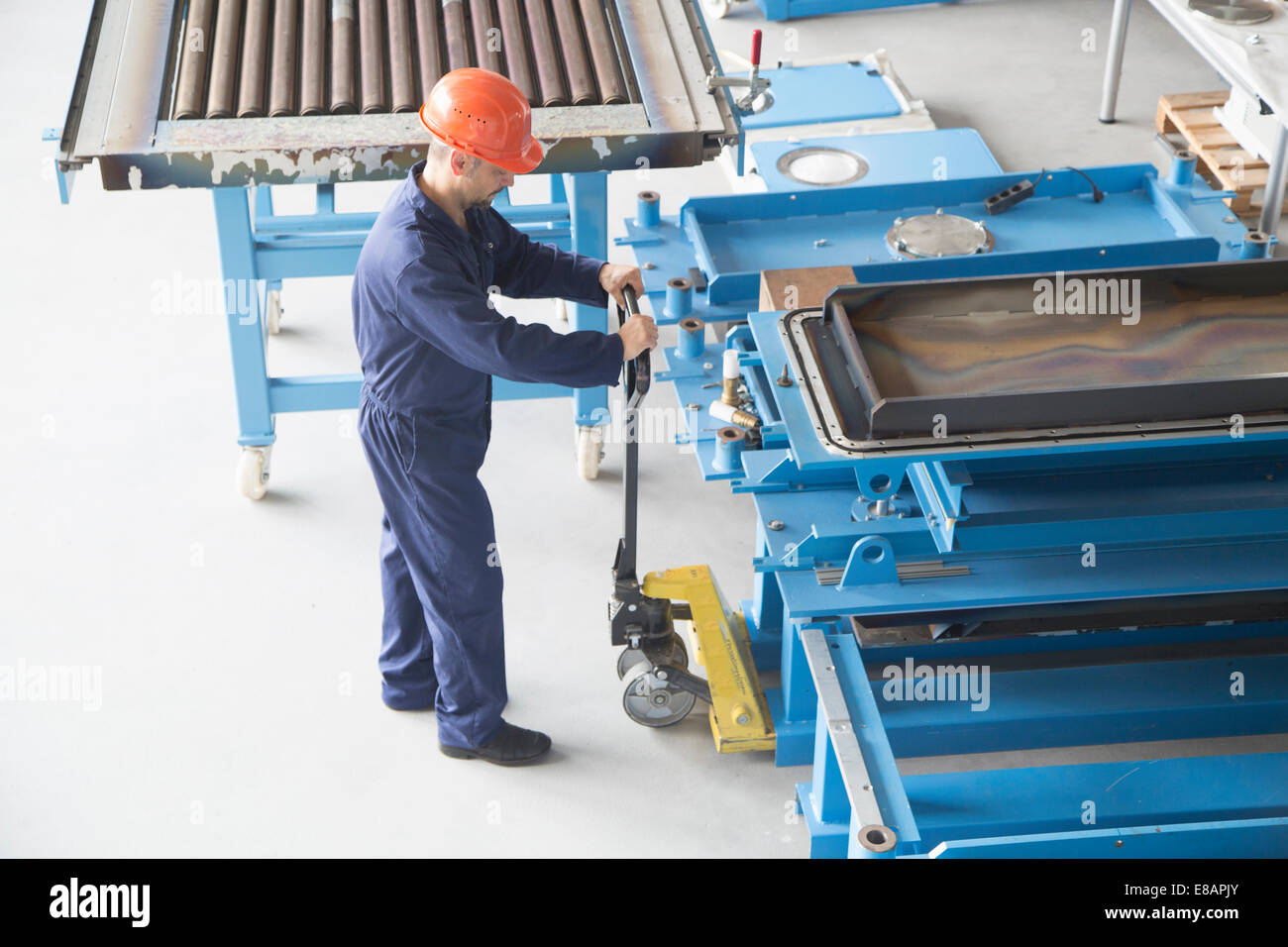 Worker using manual pallet jack in industrial plant - Stock Image