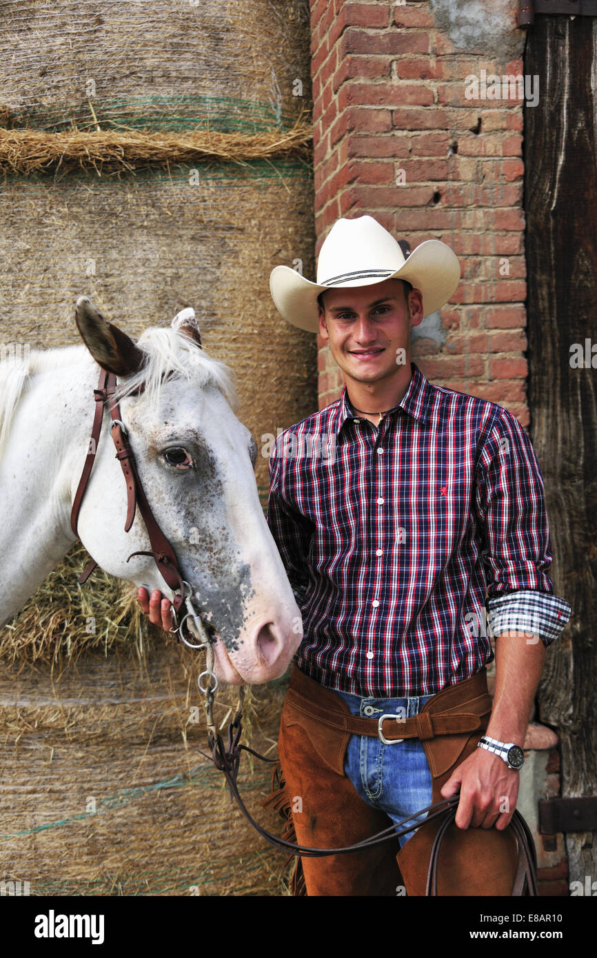 Portrait of young man in cowboy gear with horse outside stable - Stock Image