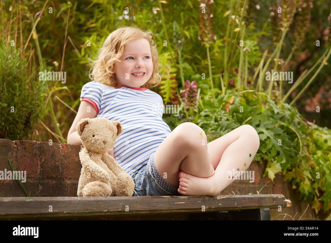 Girl on garden seat with teddy bear and star stickers on legs - Stock Image