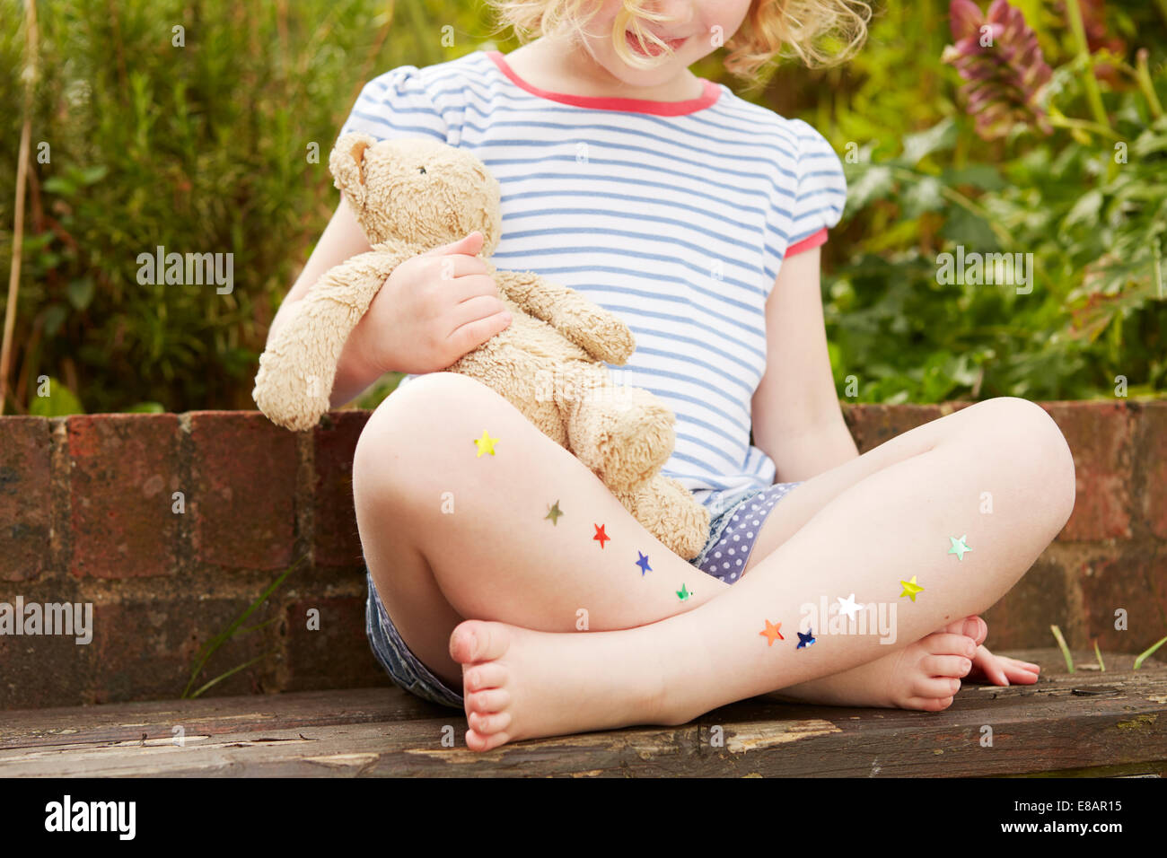 Girl on garden seat with star stickers on legs - Stock Image