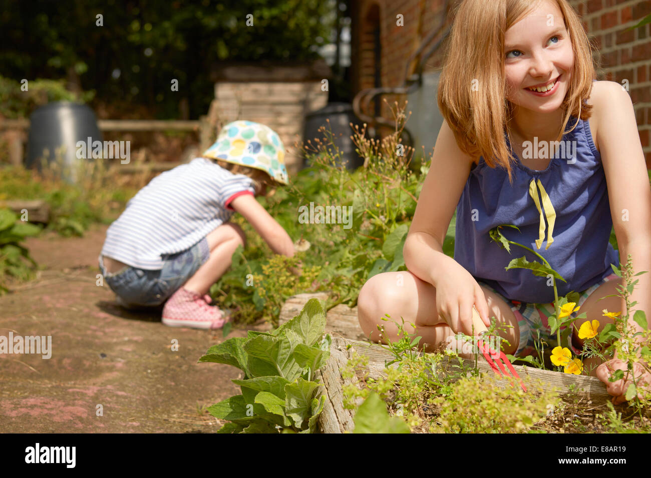 Two sisters digging in garden - Stock Image