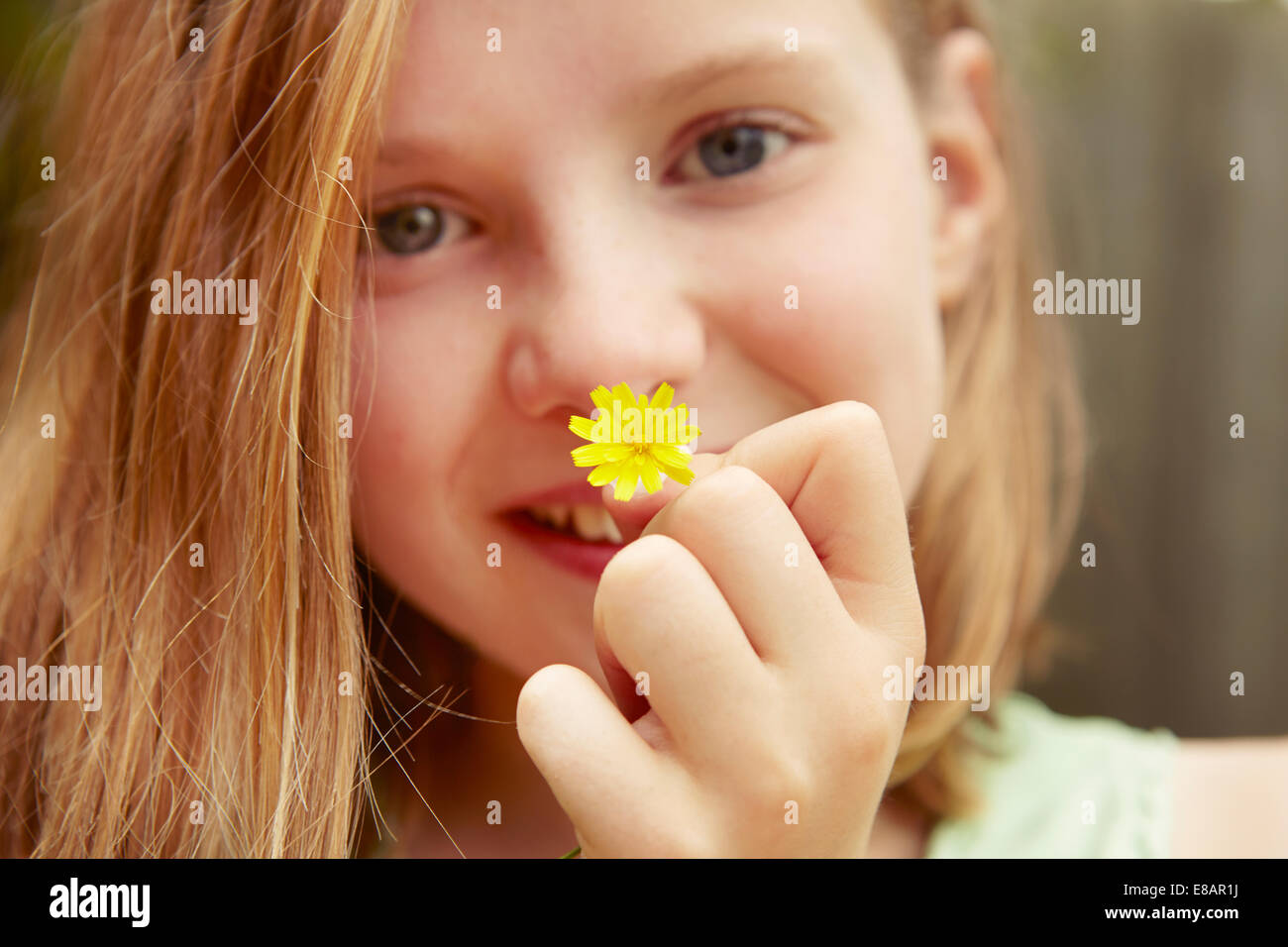 Close up portrait of girl holding dandelion flower Stock Photo