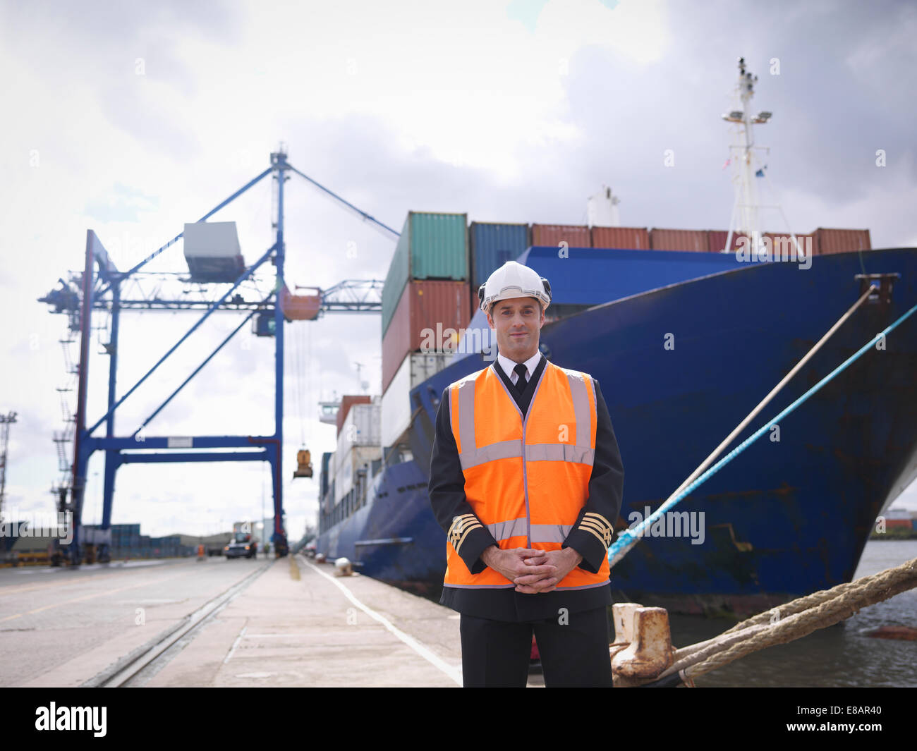 Portrait of ship's captain standing in front of container ship - Stock Image