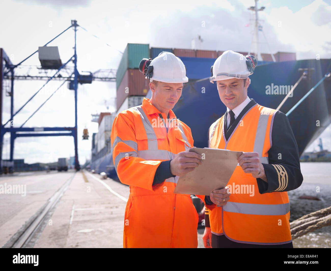 Ship's captain discussing loading cargo with port worker - Stock Image