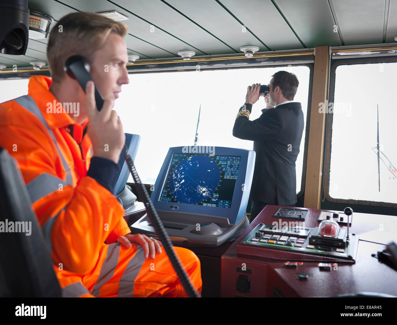 Ship worker using telephone and captain on ship's bridge - Stock Image