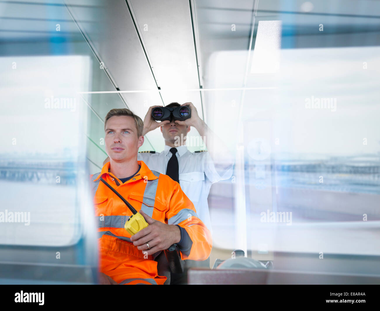 Ship worker and captain using binoculars on ship's bridge with reflections on window - Stock Image