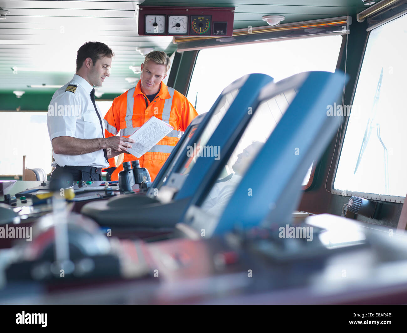 Captain and worker discussing notes on ship's bridge - Stock Image
