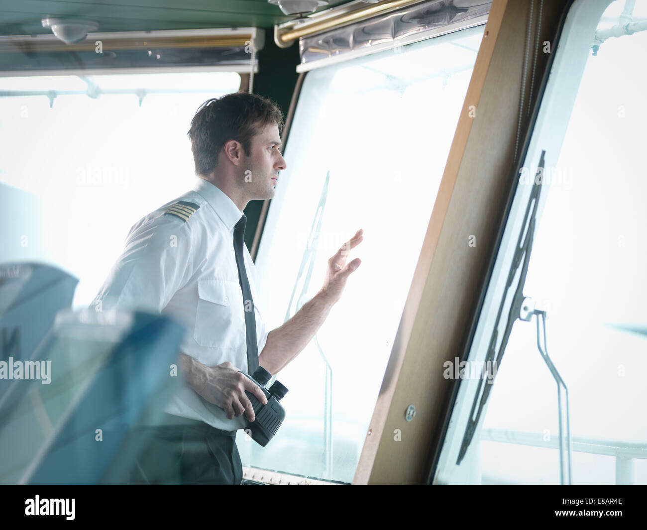 Captain looking out of window on ship's bridge - Stock Image
