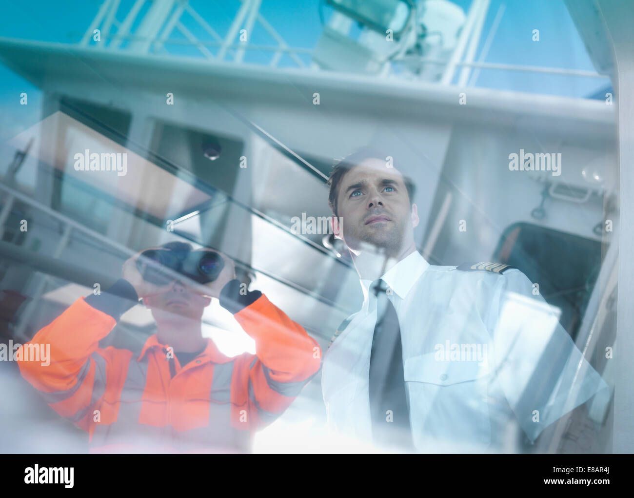 Ship's captain and worker seen through reflections on container ship - Stock Image