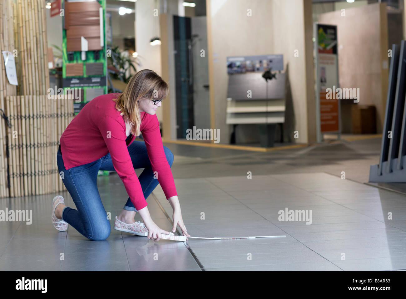 Female customer measuring floor tiles in hardware store - Stock Image