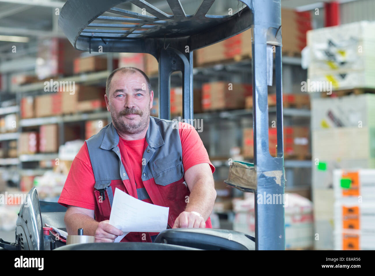 Portrait of forklift truck driver in hardware store warehouse - Stock Image