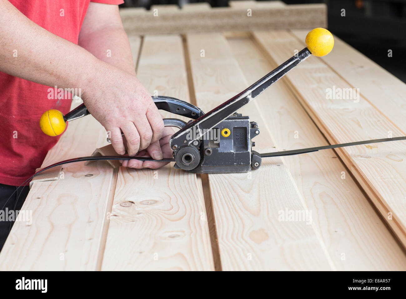 Close up of male warehouse worker fastening wooden planks in hardware store - Stock Image