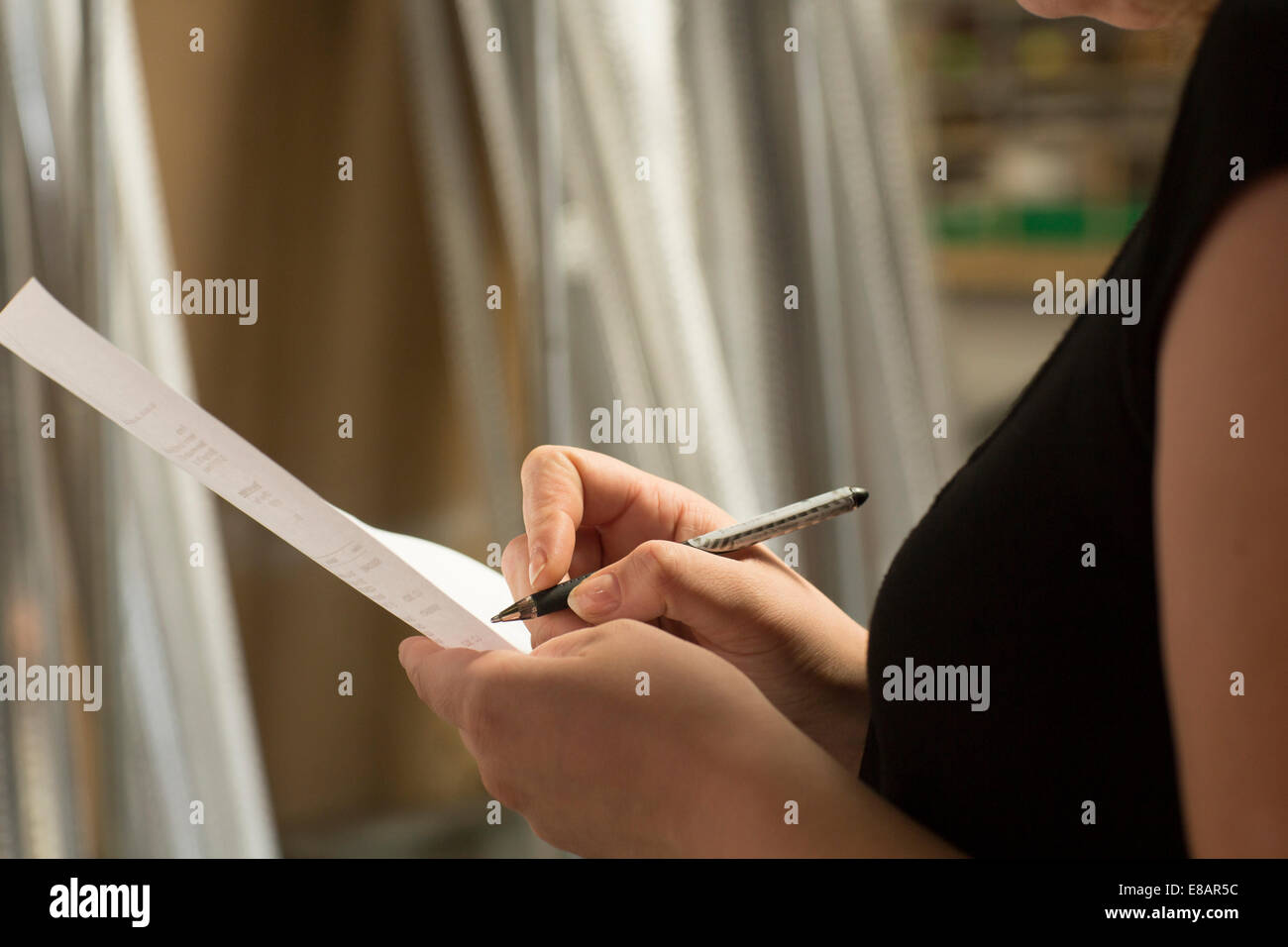 Close up of female warehouse worker taking stock in hardware store - Stock Image