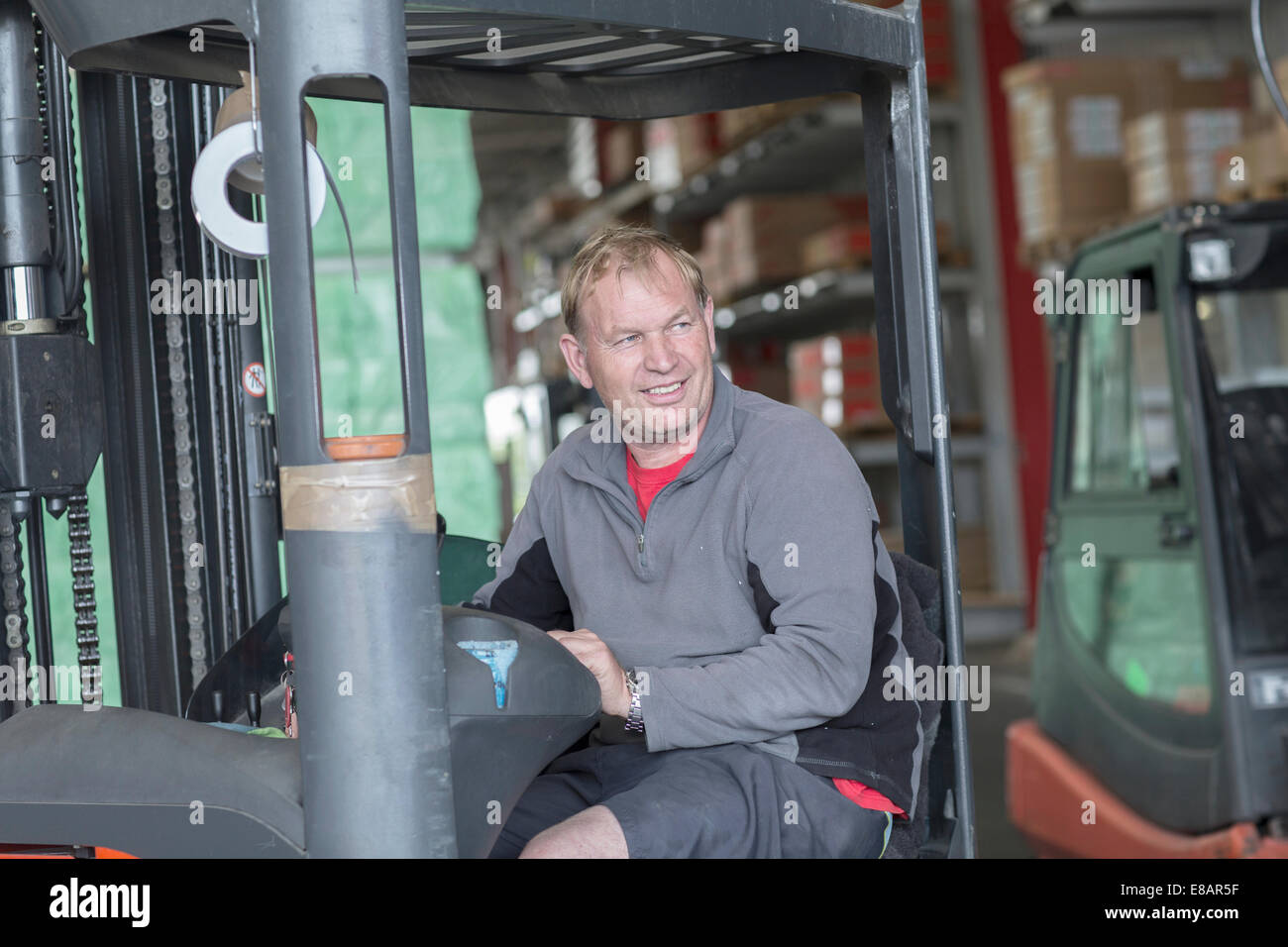 Worker driving forklift truck in hardware store warehouse - Stock Image