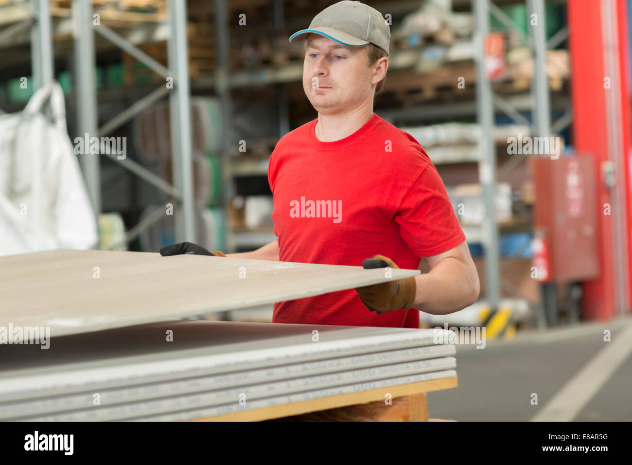 Worker lifting boards in hardware store warehouse - Stock Image