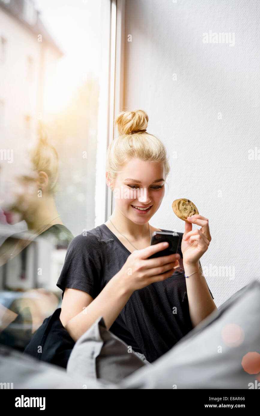Young woman reading texts on smartphone in window seat - Stock Image