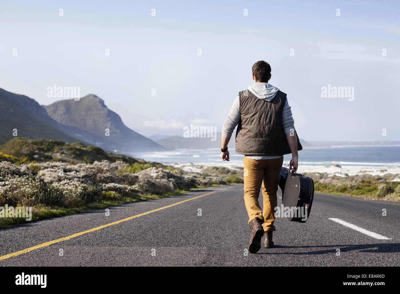Rear view of young man with guitar case walking on coastal road, Cape Town, Western Cape, South Africa - Stock Image