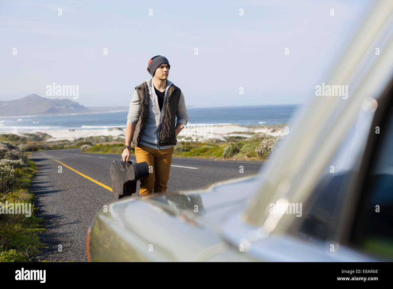 Young man behind parked car with guitar case, Cape Town, Western Cape, South Africa - Stock Image