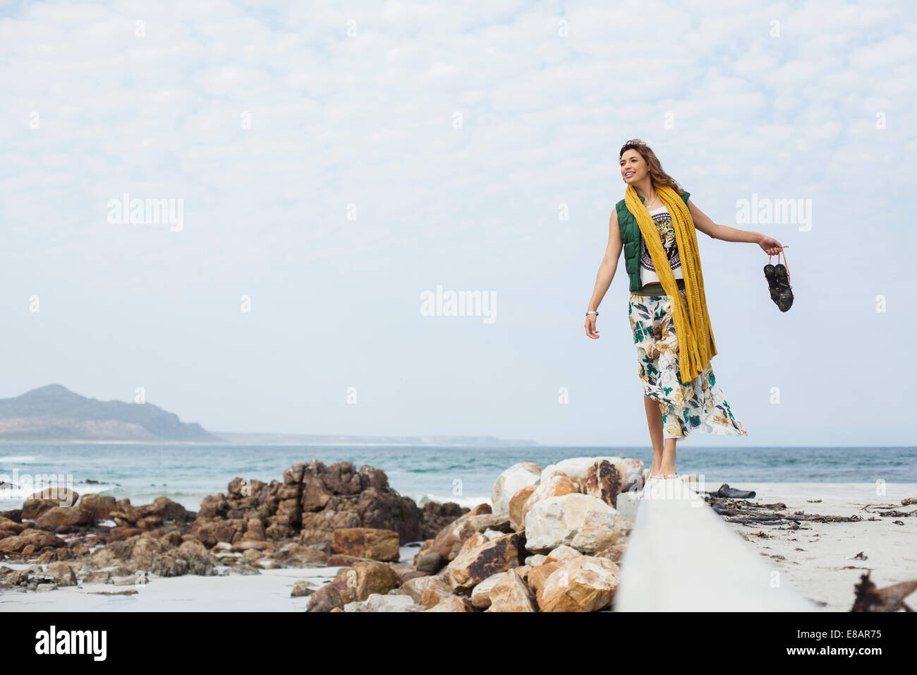 Young woman walking on cement block on beach, Cape Town, Western Cape, South Africa - Stock Image