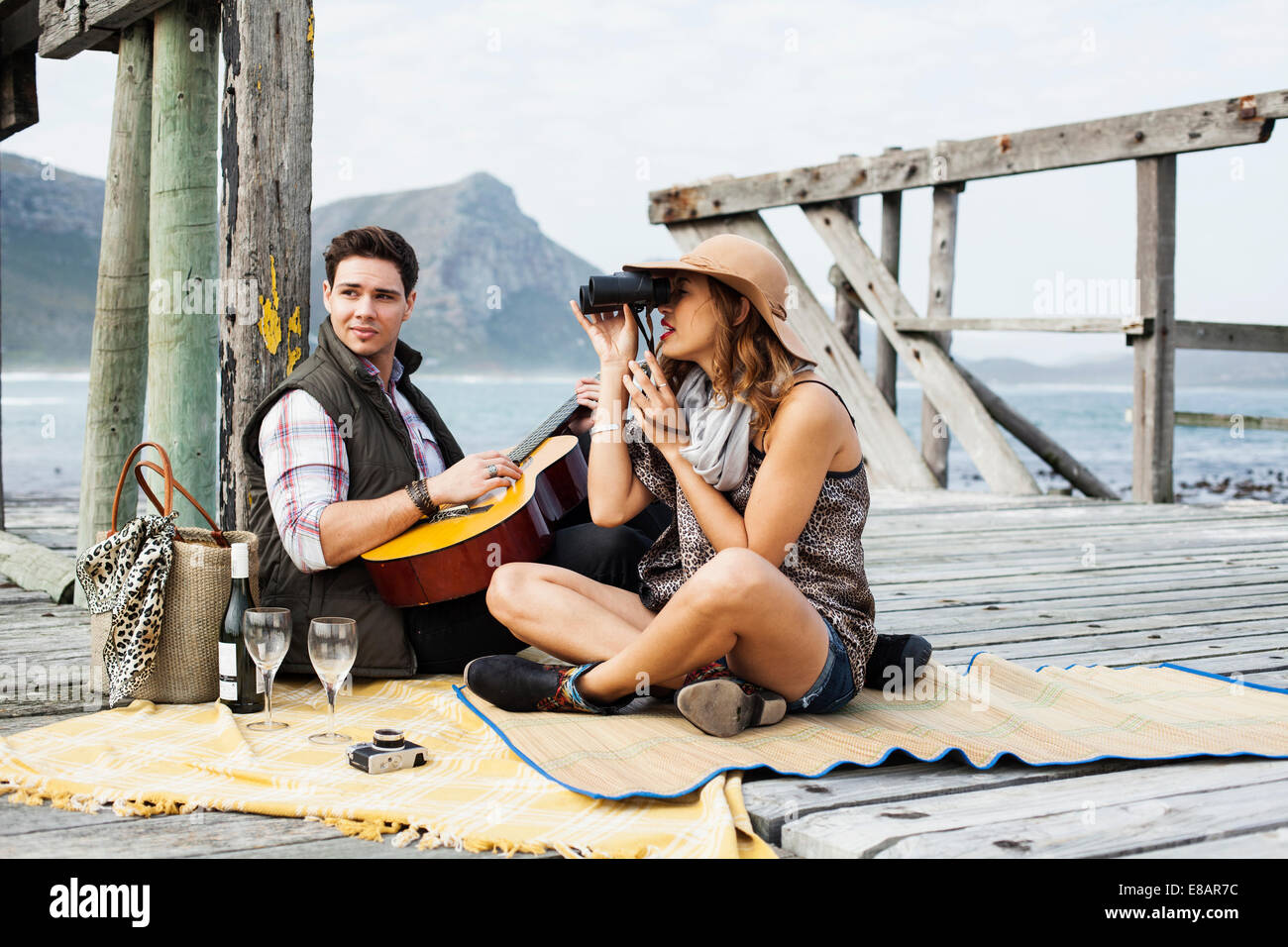 Young couple picnicing on old pier, Cape Town, Western Cape, South Africa - Stock Image