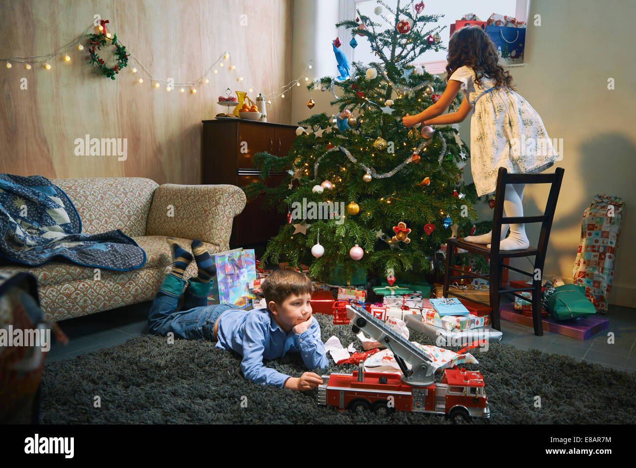 Girl arranging christmas tree whilst brother plays with xmas gifts on sitting room floor - Stock Image