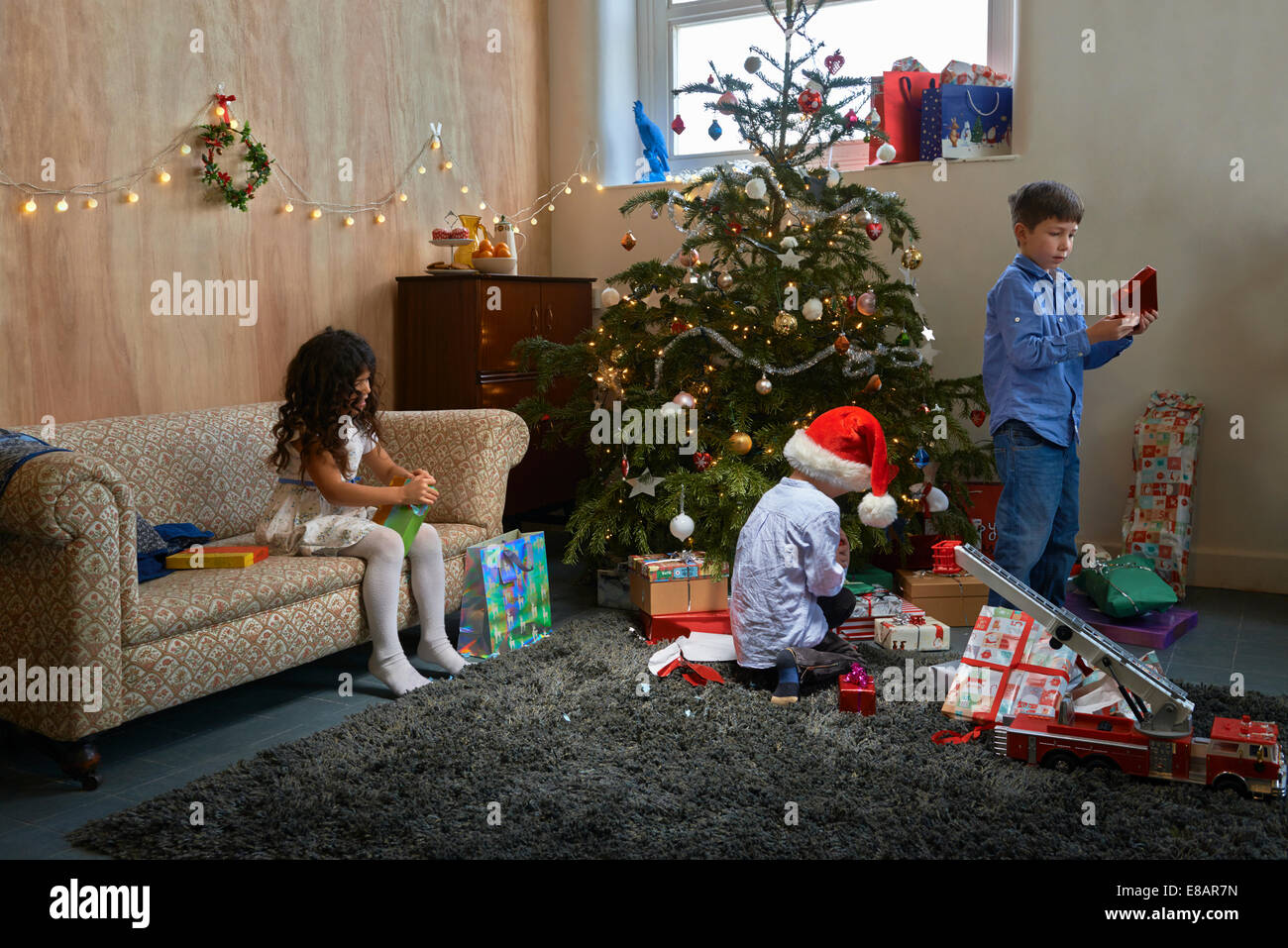 Girl and two brothers opening christmas gifts in sitting room Stock Photo
