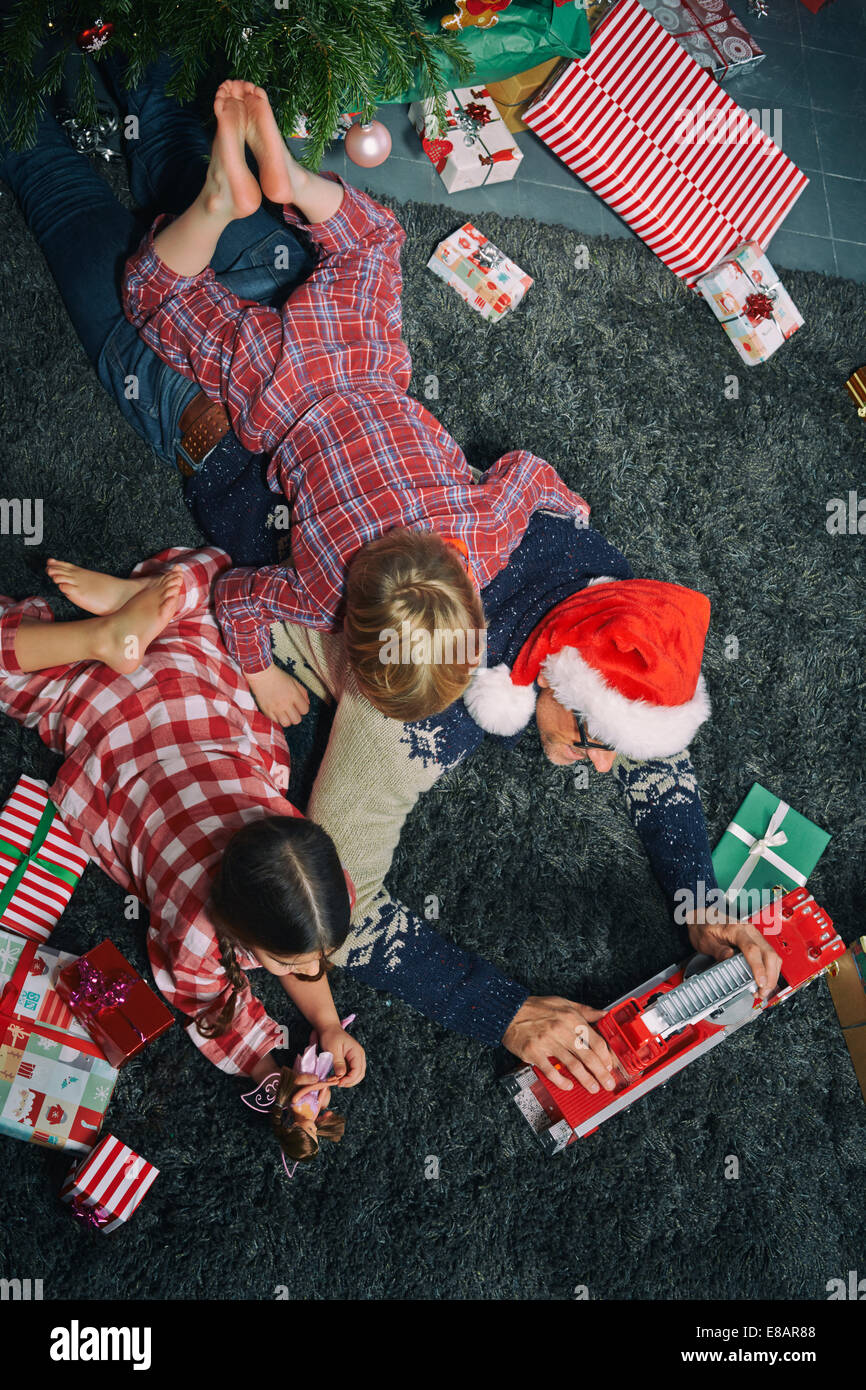 Father lying on sitting room floor opening christmas gifts with daughter and son - Stock Image