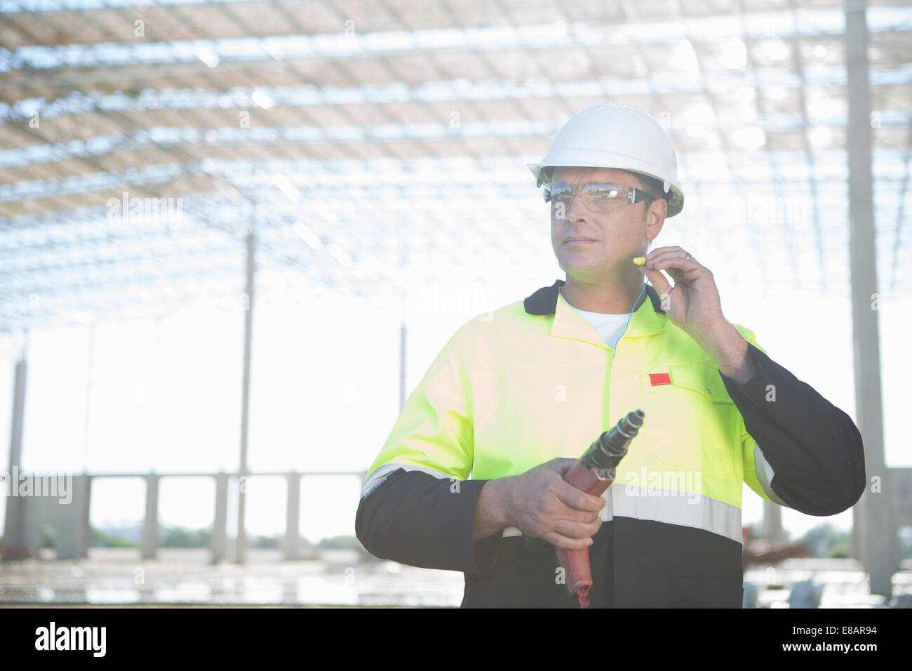 Builder with electric drill inserting earplugs on construction site - Stock Image